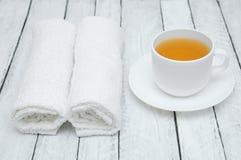 Taza y platillo blanco del té verde y dos toallas de Terry blancas en un fondo de madera blanco foto de archivo