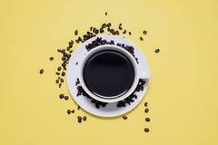 Taza y platillo de café con los granos de café derramados fotografía de archivo