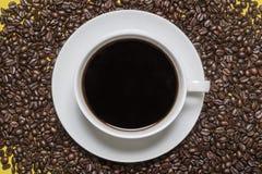 Taza y platillo de café en un fondo de los granos de café fotografía de archivo