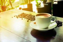 Taza y platillo de café en un vector de madera Fondo oscuro Imagen de archivo