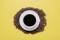 Taza y platillo de café en una cama de habas foto de archivo libre de regalías