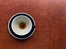 Taza y platillo de cerámica negros del café sólo caliente acabado con café marrón manchado en una taza en la tabla de madera marr imagen de archivo libre de regalías