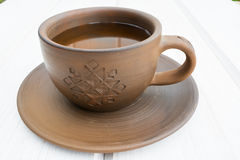 Taza y platillo de la arcilla de la taza y del platillo de la arcilla en un fondo de madera blanco Foto de archivo
