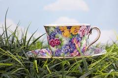 Taza y platillo florales hermosos en hierba Imágenes de archivo libres de regalías