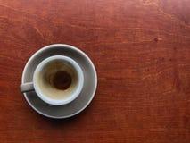 Taza y platillo grises claros del café acabado del café express con café marrón manchado en una taza en la tabla de madera marrón fotos de archivo