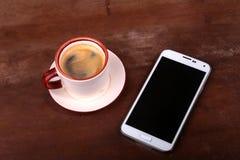 Taza y smartphone de café en la tabla de madera Visión desde arriba foto de archivo