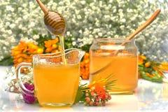 Taza y tarro de cristal con la miel y la cuchara de madera en fondo floral Imagenes de archivo