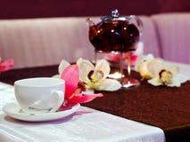 Taza y tetera de té en la tabla Foto de archivo libre de regalías