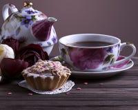 Taza y torta de té de la tetera en la tabla de madera marrón Foto de archivo