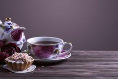 Taza y torta de té de la tetera en la tabla de madera marrón Imagen de archivo libre de regalías