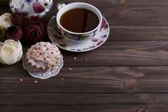 Taza y torta de té de la tetera en la tabla de madera marrón Fotos de archivo libres de regalías