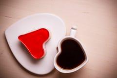 Taza y torta en forma de corazón de café Imagenes de archivo
