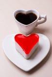 Taza y torta en forma de corazón de café Foto de archivo