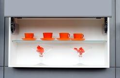 Tazas anaranjadas en estante Foto de archivo libre de regalías