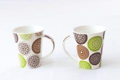Tazas blancas con diseño coloreado Imagen de archivo libre de regalías