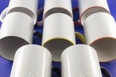Tazas blancas con las plumas coloreadas en un fondo azul Fotografía de archivo libre de regalías