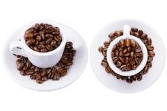 2 tazas blancas con los granos de café Imagenes de archivo