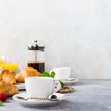 Tazas blancas de café y de cruasanes Fotos de archivo libres de regalías