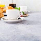 Tazas blancas de café y de cruasanes Imágenes de archivo libres de regalías