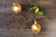 Tazas blancas de capuchino en una tabla de madera con los granos de café Imagen de archivo