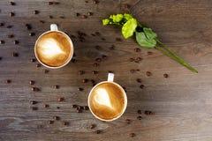 Tazas blancas de capuchino en una tabla de madera con los granos de café Fotografía de archivo libre de regalías