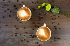 Tazas blancas de capuchino en una tabla de madera con los granos de café Fotografía de archivo