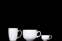 Tazas blancas en fondos negros foto de archivo