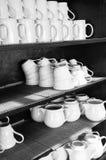 Tazas blancas en estantes Fotos de archivo libres de regalías