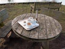 tazas blancas usadas en la bandeja en la tabla de madera fuera del café Foto de archivo