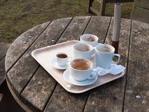 tazas blancas usadas en la bandeja en la tabla de madera fuera del cierre del café para arriba Foto de archivo libre de regalías