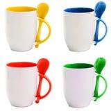 Tazas coloreadas con las cucharas Foto de archivo libre de regalías