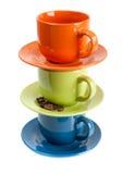 Tazas coloreadas con los granos de café en el fondo blanco Fotografía de archivo libre de regalías