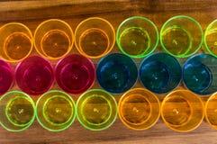 Tazas coloreadas del partido - amarillas, anaranjadas, rosadas y azul alineó en tres filas en un tablero de madera Imagen de archivo libre de regalías