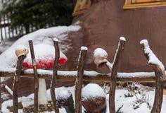 Tazas coloreadas en una cerca de madera en un pueblo del invierno Foto de archivo libre de regalías