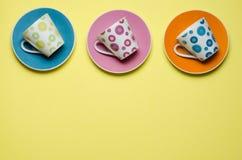 Tazas coloridas en los platillos Imágenes de archivo libres de regalías