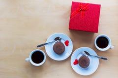 Tazas con café, la caja de regalo y los coockies en la tabla de madera Imagenes de archivo