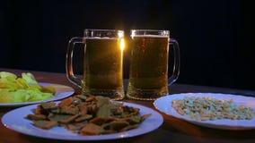 Tazas con la cerveza ligera que hace espuma en una tabla de madera contra un fondo negro almacen de metraje de vídeo