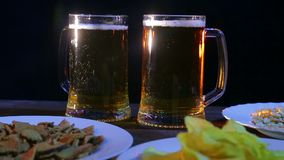 Tazas con la cerveza ligera que hace espuma en una tabla de madera contra un fondo negro metrajes