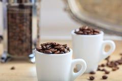 Tazas con los granos de café Fotografía de archivo