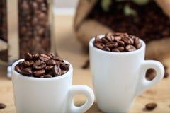 Tazas con los granos de café Imágenes de archivo libres de regalías