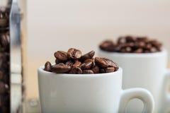 Tazas con los granos de café Imagen de archivo