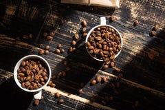 Tazas con los granos de café en la luz del sol de la mañana Fotografía de archivo