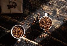 Tazas con los granos de café en la luz del sol de la mañana Fotos de archivo