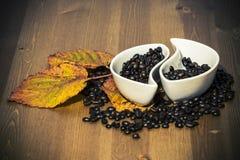 Tazas con los granos de café en una tabla de madera Foto de archivo