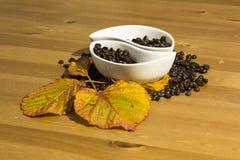 Tazas con los granos de café en una tabla de madera Fotografía de archivo