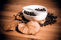 Tazas con los granos de café en una tabla de madera Imagenes de archivo