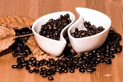 Tazas con los granos de café en una tabla de madera Imagen de archivo libre de regalías