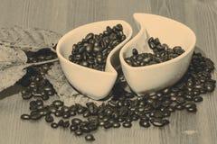 Tazas con los granos de café en una tabla de madera Imágenes de archivo libres de regalías