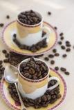 Tazas con los granos de café salteados Imágenes de archivo libres de regalías