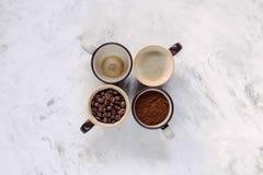 Tazas con los granos de café, una roca y bebido una taza en una tabla de cocina blanca Imagen de archivo libre de regalías